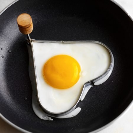 Heart-shaped egg in frying pan with mold